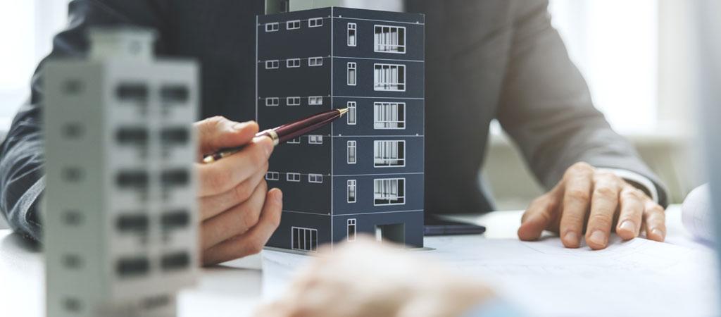 Mitarbeiter bespricht Baumaßnahmen anhand Musterhaus